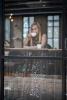 vacker kvinna på ett kafé som dricker kaffe foto
