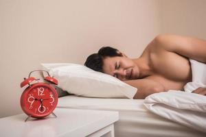 mannen sover i sängen med röd väckarklocka foto