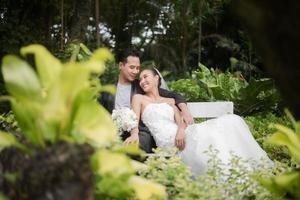 bruden och brudgummen sitter på filialen med den gröna parkbakgrunden
