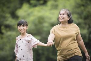 mormor som leker med barnbarnet utomhus i parken foto