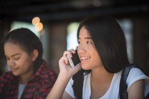 unga kvinnor som använder och tittar på smarttelefonen på fönsterkaféet foto