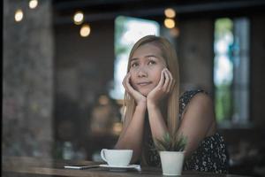 stående av en ung kvinna som ler i kafékafé foto