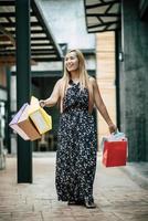 porträtt av en ung glad kvinna med påsar som går på gatan foto