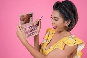 porträtt av en kvinna med smink och kosmetisk borste