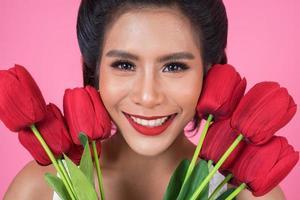 porträtt av en vacker kvinna med bukett med röda tulpanblommor foto