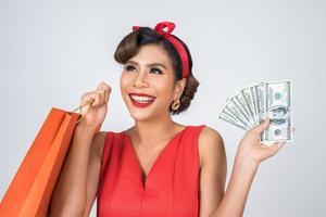vacker asiatisk kvinna med färgade shoppingpåsar och pengar