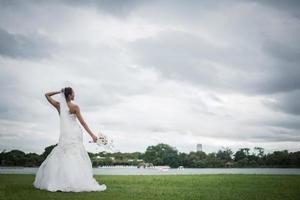 vacker brud med blommor, bröllopsmakeup och frisyr foto