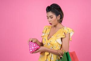 ung moderiktig kvinna som håller en plånbok med kontanter och påsar