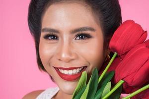 porträtt av en vacker kvinna med bukett med röda tulpanblommor