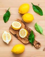 färska citroner och blad på en rustik träbakgrund foto
