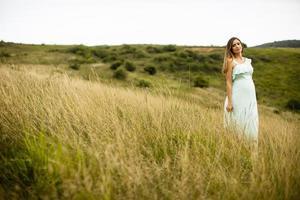 ung gravid kvinna som kopplar av utanför i naturen foto