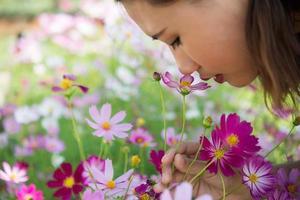 närbild av glad kvinna som luktar kosmosblommor i en trädgård