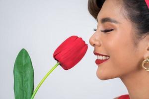 porträtt av en vacker kvinna med röda tulpanblommor foto