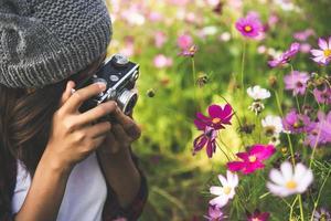 hipster tjej med vintage kamera fokus skytte blommor i en trädgård foto