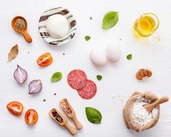 ingredienser för pizza på vit träbakgrund foto