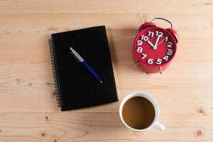 röd väckarklocka med anteckningsblock och kaffe på träbord foto