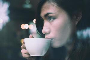 ung kvinna i café dricker kaffe, njuter av avkopplande tid foto