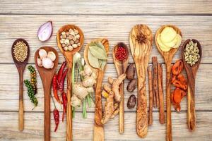olika kryddor och örter i träskedar foto