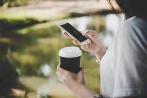 ung kvinna som håller engångskaffe kopp medan textmeddelanden genom smartphone utomhus