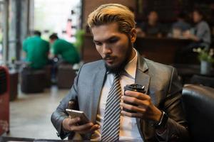 affärsman som sitter på kafé med mobiltelefon foto