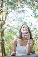 ung kvinna som håller disponibel kaffekopp medan du sitter utomhus