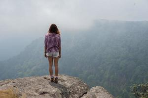 baksida av vandrare som står på toppen av ett berg och njuter av naturvyn