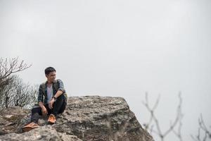 ung hipster vandrare med ryggsäck sitter på toppen av berget foto