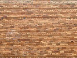 gammal vägg med gula och bruna tegelstenar