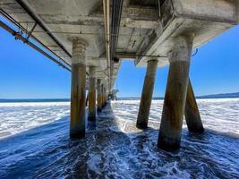 under en lång betongbrygga vid havet