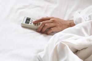 hand som håller luftkonditionering fjärrkontroll på sängen foto