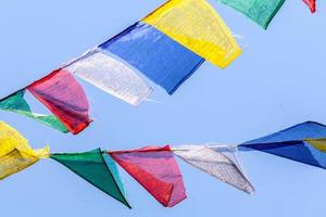 buddhistiska bönflaggor i en blå himmel foto