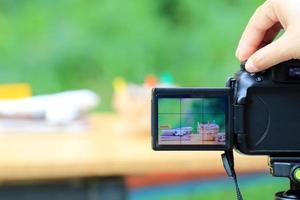 hand med digitalkamera som fotograferar skrivbordsinstallation med flygplan och pengarsäckar
