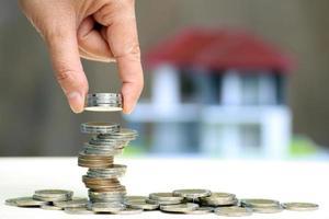 hand stapla mynt med ur fokus hus i bakgrunden