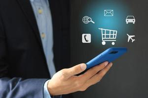 konceptbild av affärsmaninnehav mobiltelefon med flytande applikationsikoner