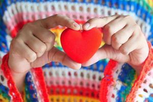 kvinna som håller en röd hjärtanärbild foto