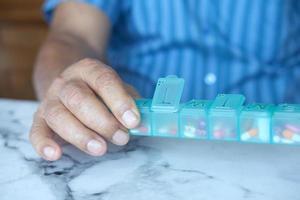 äldre mans händer som tar medicin från en pillerbox foto