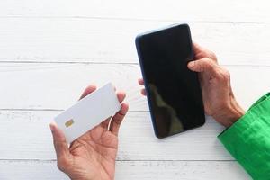 äldre kvinna som innehar ett kreditkort och använder en smartphone för att handla online foto