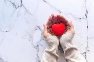 kvinna som rymmer en röd hjärta på kakelbakgrund, ovanifrån foto