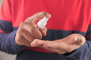 närbild av en ung man som använder handdesinfektionsspray foto