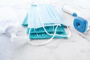 kirurgiska masker, termometer och handdesinfektionsmedel på vit bakgrund
