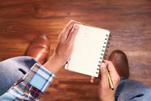 sikt för hög vinkel av en man som sitter på en stol som håller en anteckningsblock