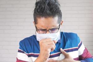ung asiatisk man hostar och nysar foto