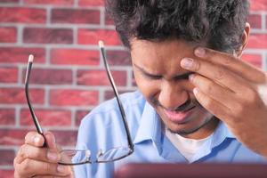 närbild av upprörd man som lider av stark ögonsmärta