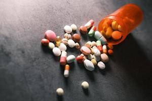 närbild av många färgglada piller och kapslar på svart bakgrund