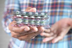 närbild av handen håller medicin blisterförpackningar foto
