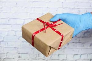 manlig hand i en blå medicinsk handske ger en gåva