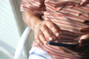 närbild av en äldre man som använder en smartphone hemma foto
