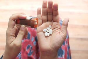 närbild av kvinnans hand som tar piller