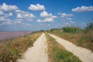 grusväg bredvid sjön med molnig blå himmel i Ryssland