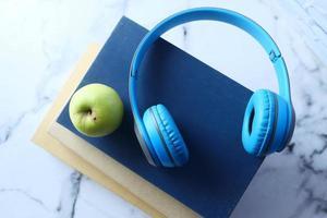 hörlurar och bok med grönt äpple över kakelbakgrund foto